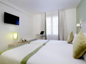 Cama ou camas em um quarto em Kyriad Paris 18 - Porte de Clignancourt - Montmartre