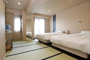 A bed or beds in a room at Dormy Inn Global Cabin Asakusa