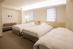 A bed or beds in a room at Shin-Osaka Station Hotel Annex