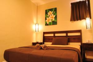 A bed or beds in a room at Bemo Corner Guest House