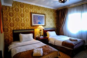 A bed or beds in a room at Sharjah International Airport Hotel
