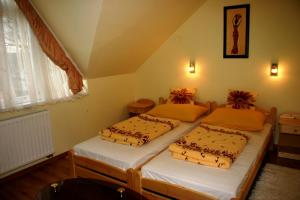 A bed or beds in a room at Ludas Fogadó