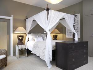 A bed or beds in a room at Windfalls Boutique Hotel