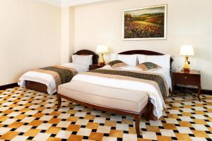 A bed or beds in a room at Royal Tulip Almaty Hotel