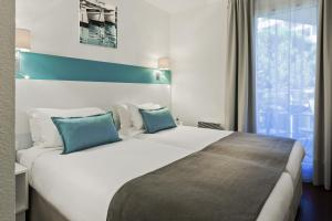 A bed or beds in a room at Citadines Castellane Marseille