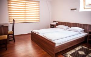 A bed or beds in a room at Pensiunea Acasa