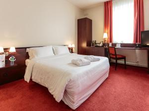 A bed or beds in a room at Kyriad Prestige Hotel Clermont-Ferrand