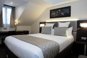 Un ou plusieurs lits dans un hébergement de l'établissement Hotel Choiseul Opera