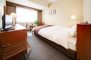 A bed or beds in a room at Meitetsu Grand Hotel