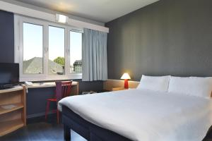A bed or beds in a room at Ibis Brive Centre