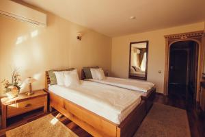 A bed or beds in a room at Denisa Boutique Hotel
