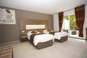 A bed or beds in a room at The Originals City, Hôtel Les Bastides du Gapeau