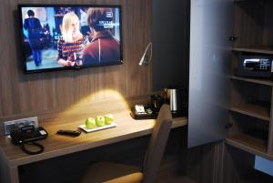 A television and/or entertainment centre at Dom Hotel Am Römerbrunnen