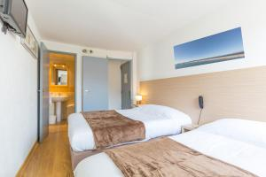 A bed or beds in a room at Europe Hotel Vieux Port