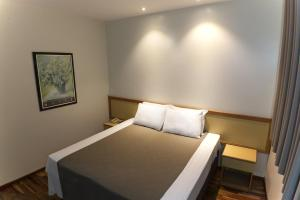 A bed or beds in a room at Summit Inn Hotel Pouso Alegre