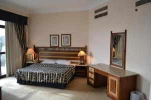 A bed or beds in a room at Om Kolthoom Hotel