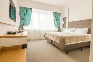 A bed or beds in a room at Gardenia Hotel & Spa