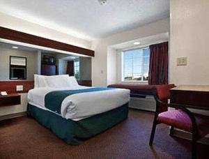 A bed or beds in a room at Microtel Inn by Wyndham Spartanburg Duncan