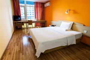 Кровать или кровати в номере 7Days Inn Yantai Huangshan Road