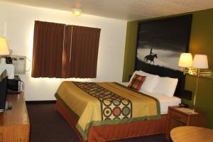 A bed or beds in a room at Super 8 by Wyndham Ruidoso