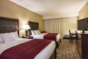 A bed or beds in a room at Grand Oaks Hotel