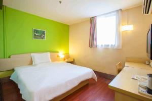 Кровать или кровати в номере 7Days Inn Yantai Changjiang Road Jindong Community