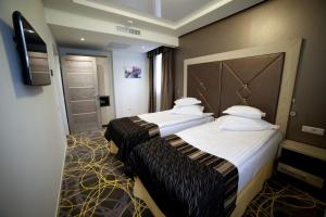 A bed or beds in a room at Exclusive Hotel & More