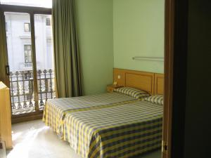 A bed or beds in a room at Hostal Nuevo Colon
