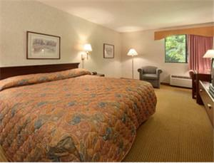 A bed or beds in a room at Super 8 by Wyndham West Springfield/Route 5