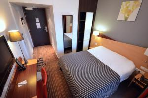 A bed or beds in a room at Kyriad Hotel Dijon Gare