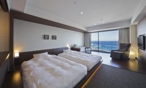 A bed or beds in a room at Atami Seaside Spa & Resort