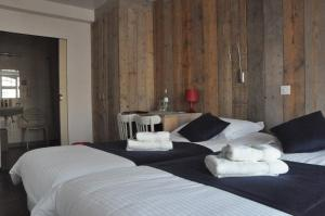 A bed or beds in a room at Hotel Aan Zee