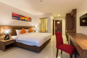 A bed or beds in a room at Riche Hua Hin Hotel