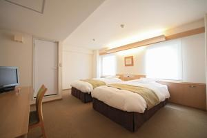 A bed or beds in a room at Shin-Osaka Station Hotel