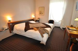 A bed or beds in a room at Nouvel Hotel