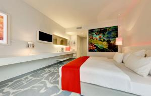 A bed or beds in a room at art'otel cologne, part of Radisson Hotel Group