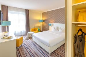 A bed or beds in a room at Ibis Styles Regensburg
