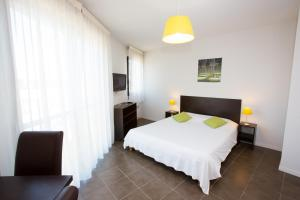 A bed or beds in a room at All Suites Pau – Zénith