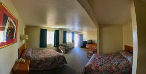 A bed or beds in a room at Travelers Inn Topeka