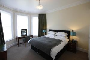 A bed or beds in a room at Glenlyn Hotel