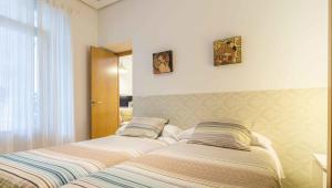 A bed or beds in a room at La Casa del Conde de Gelves Apartments