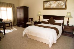 A bed or beds in a room at 26 On Chamberlain Guest House