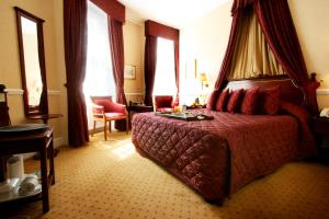A bed or beds in a room at Grange Blooms Hotel