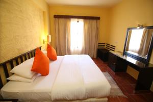A bed or beds in a room at Tamra Beach Resort