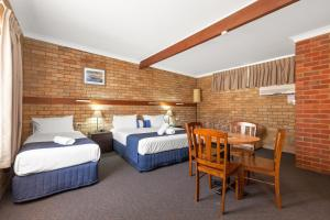 A bed or beds in a room at Gulgong Motel