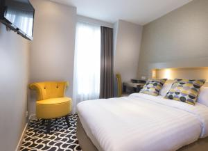 A bed or beds in a room at Hôtel International Paris