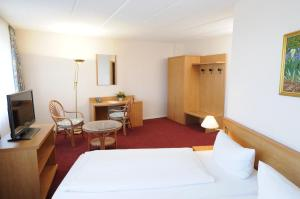 A bed or beds in a room at AXXON Hotel