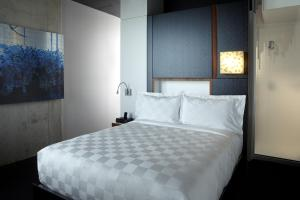 A bed or beds in a room at Alt Hotel Toronto Airport