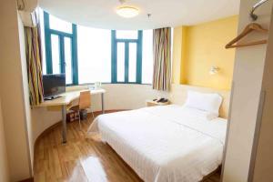 Кровать или кровати в номере 7Days Inn Yantai Fuhai Road