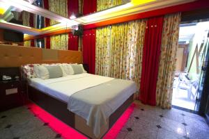 A bed or beds in a room at Status Motel (Adult Only)